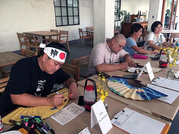 "Artists hard at work at a reception held before the screening of ""Miss Hokusai"" Oct. 1. From left are Jon Murakami (with FIGHTING SPIRIT HEADBAND~!), Michael Cannon, Kaci Horimoto and Tara Tamayori."